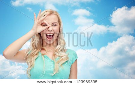 fun, emotions, expressions and people concept - smiling young woman or teenage girl making ok hand gesture over blue sky and clouds background