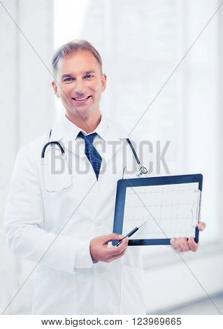 healthcare and medical concept - male doctor with stethoscope showing cardiogram