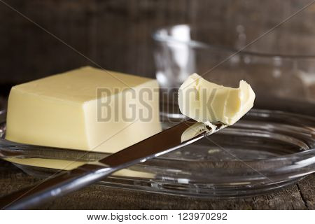 Knife with butter and butter dish in background