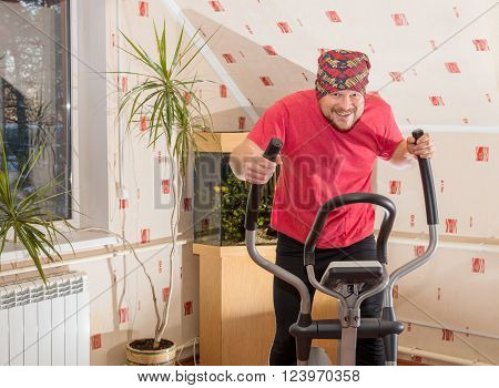 Middle aged man running on simulator at home interior