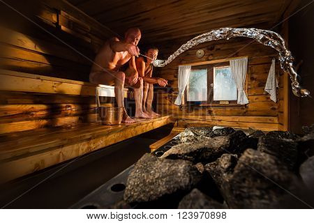 Middle aged couple in traditional wooden Finnish sauna, man throwing water to hot stove