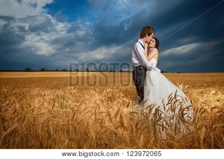 In Love Couple In Wheat Field With Blue Dramatic Sky