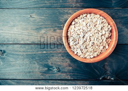 Oat flakes in bowl on turquoise wooden background