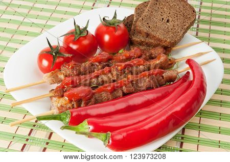 Shashlik on a plate with cherry tomatoes and chili.