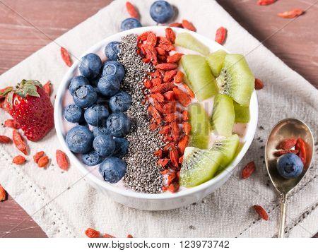 Smoothie bowl with yogurt strawberry smoothie goji berries blueberries chia seeds and kiwi on napkin