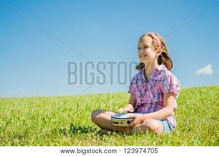 Cute teen girl playing tambourine sitting on grass in nature