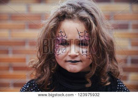 Madrid Spain little girl with spider web painted on sad face looking at camera. Halloween