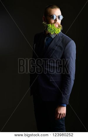Fashion shot of a handsome man with a beard of green flowers. Men's beauty. Barbershop.