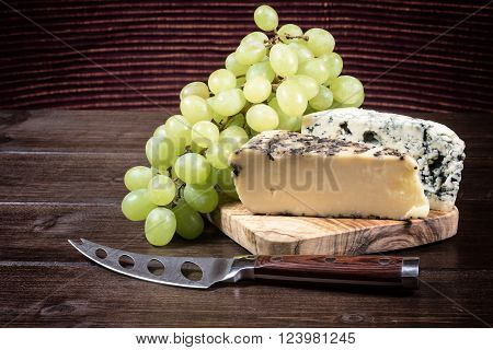 Two kinds of cheese and grapes of the white wine are lying on the board of olive wood. Stainless steel cheese knife is lying on a wooden board in foreground. Photo is edited as an vintage with dark edges.