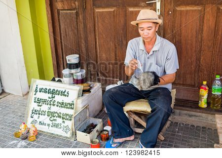 Siem Reap, Cambodia, 15 Nov 2015: Traditional shoe repairman carrying out repairs by putting glue on old shoe.