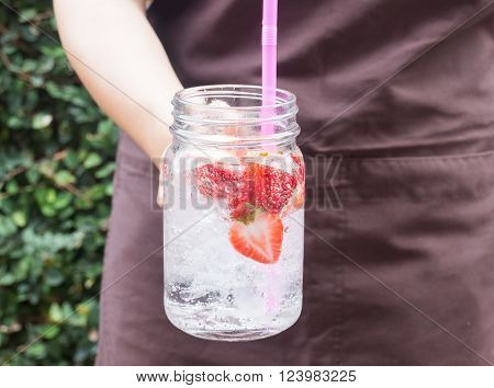 Hand on serving glass of iced strawberry soda drink stock photo