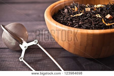 Dried tea leaves in bamboo bowl and tea strainer on wooden background