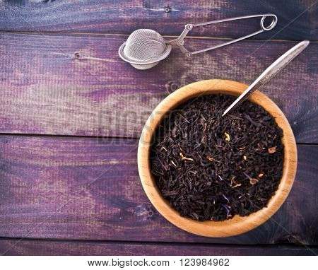 Dried tea leaves in beige bowl with teaspoon and tea strainer on wooden background. Copy space