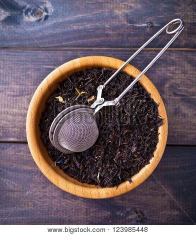 Dried tea leaves in bamboo bowl and tea strainer on wooden background. Top view