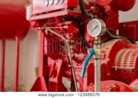 old pressure gauge and red generator machine in background