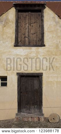 Facade of old medieval house. Historical front age house. Rural entry architecture element. Big wooden old door, closed brown. Exterior situation. Old town background.