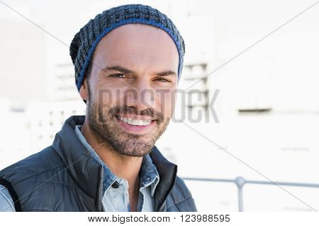 Portrait of confident young man wearing beanie hat and jacket