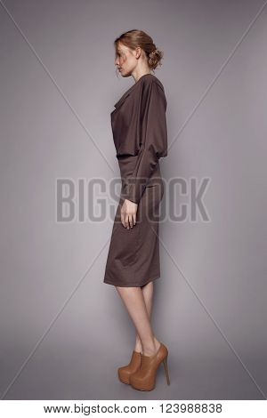 Beautiful Woman in stylish silk Dress posing in studio