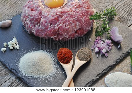 Minced meat with spices, egg and bread crumbs on a wood backgraund.