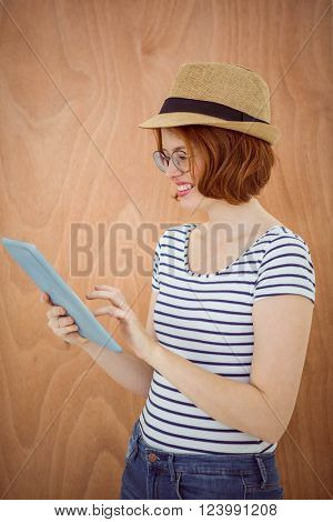 smiling hipster woman, wearing a trilby, on her tablet computer