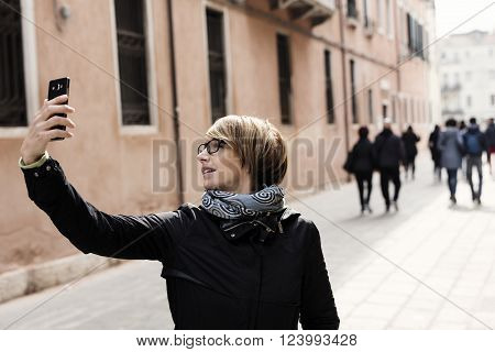 Traveling around the world. Beautiful modern woman making selfie. Local sights in the background.