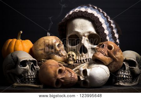 still life human skulls on black background and yellow pumkin