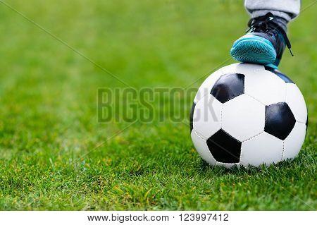 Feet Of Child On Football / Soccer Ball On Grass.