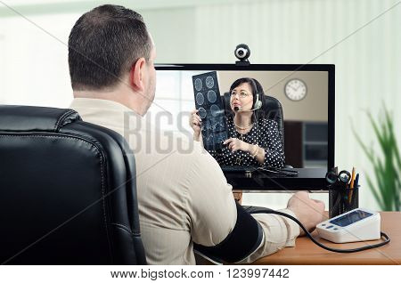 Middle-aged man measures his blood pressure in front of virtual doctor. In the meantime telemedicine physician is carefully looking at his brain x ray picture in the monitor. Horizontal shot