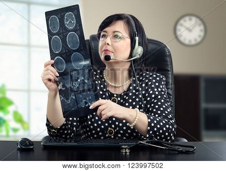 Telemedicine doctor in headphones is looking at x ray picture of brain carefully. Black haired doctor in glasses sitting at black desk. She is wearing a polka dot blouse. Horizontal shot
