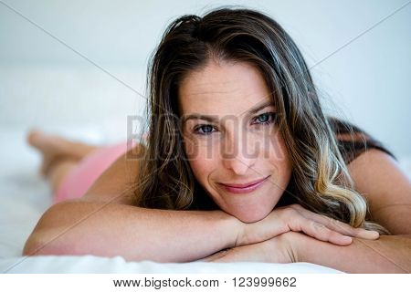 smiling barefoot woman, lying on her bed, looking at the cameraa