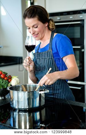 smiling woman cooking vegtables in a saucepan on a stove top and drinking red wine