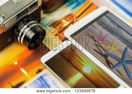 Old analog camera, smartphone and tablet, with colorful summertime pictures
