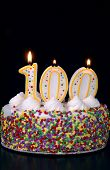 pic of centenarian  - a colorful birthday cake with candles shaped like the number 100 - JPG