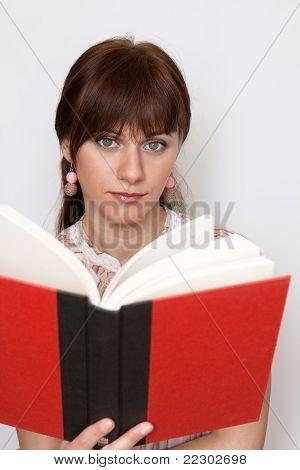Süße junge Brünette in ein Rosafarbenes Hemd, das Buch zu lesen
