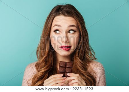 poster of Portrait of a lovely brown haired woman with bright makeup eating chocolate bar isolated over blue b