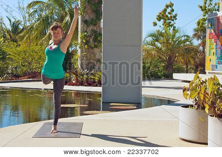 Woman Doing Yoga Outdoors In Dancer Variation Pose Front View
