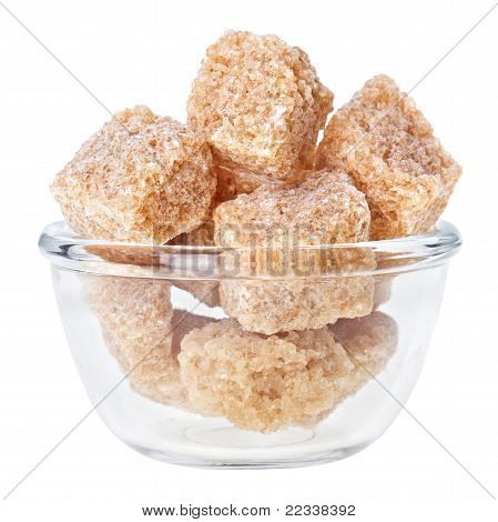 Brown Lump Cane Sugar In A Glass Bowl, Isolated On White