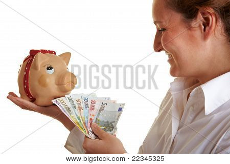 Business Woman Feeding Piggy Bank With Money