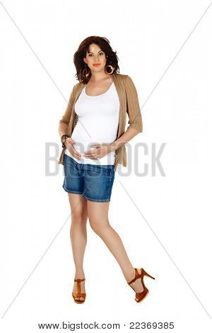 beautiful eight months pregnant brunette woman wearing fashion shorts and high heels over white studio background.
