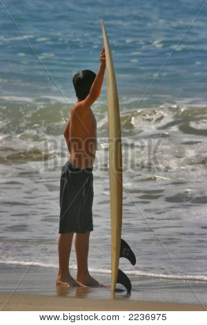 Boy Holding Surfboard On Beach