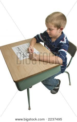 Boy Writing On School Desk