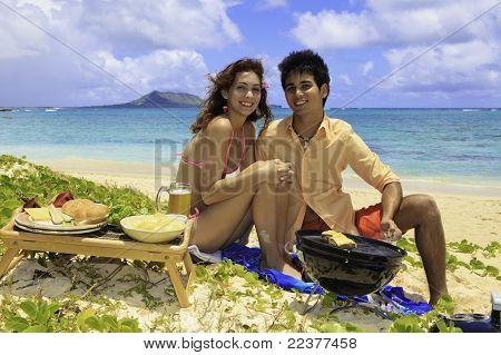 couple having a beach barbecue