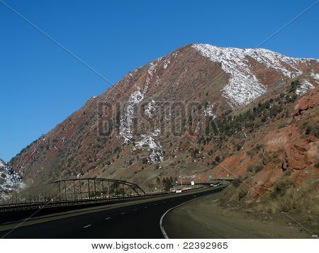 Red Sandstone Cliffs Above Winter Highway And Traffic