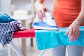 Woman wife doing ironing at home poster