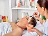 Mud facial mask of man in spa salon. Massage with mud from full face. Male lying spa bed. Beautician poster