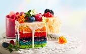 Various slices of cakes on a white tray: rainbow cake, raspberry cake and almond cake. Sweets decora poster