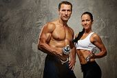 image of fitness man body  - Athletic man and woman with a dumbells - JPG