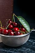 Several Red Sweet Cherries On The Table. Fresh Organic Cherry In Yellow Wooden Basket On Dark Marble poster