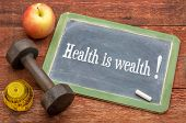 health is wealth concept -  slate blackboard sign against weathered red painted barn wood with a dum poster