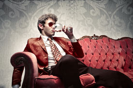 stock photo of red wine  - Young man sitting on a sofa and drinking some wine - JPG